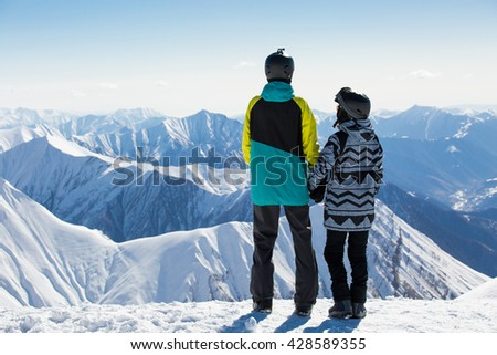 Couple in love snowboarder snowboarding on fresh white snow on ski slope on Sunny winter day - stock photo