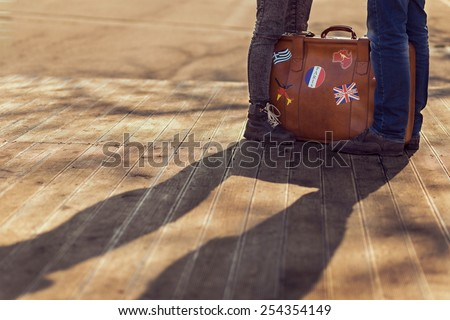 Couple in love standing next to a suitcase - stock photo