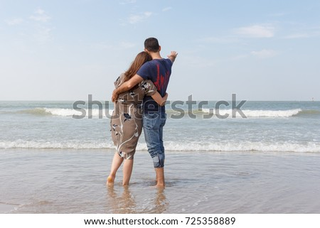 Couple in love standing on the beach looking into the distance.