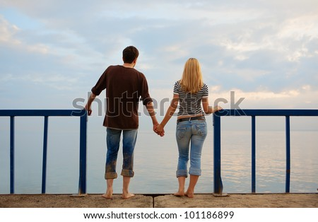 couple in love standing on the edge of the pier, and looks into the distance. Summer evening - stock photo