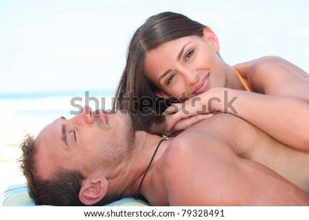 Couple in love sunbathing on the beach - stock photo