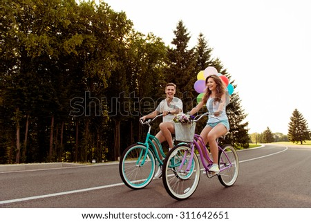 couple in love together to ride a bicycle with ballons - stock photo