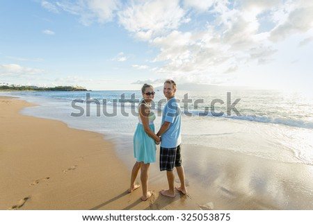 Couple in love walking along the beach together - stock photo