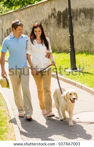 Couple in love walking Labrador dog in park sunny day - stock photo