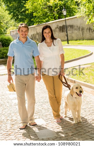 Couple in love walking Labrador dog in park sunny day