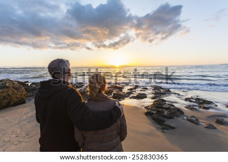 Couple in love watching a sunset on the beach, moment of reflection - stock photo