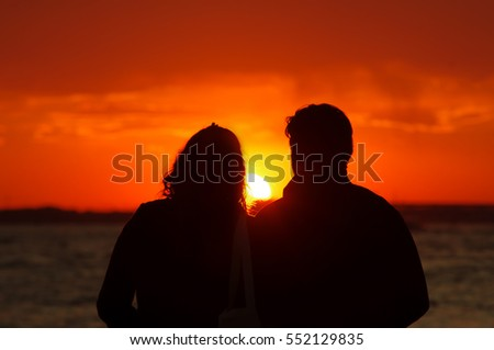 couple in love watching sunset on sea