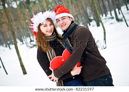 Couple in love with a red heart and Christmas Hats - stock photo