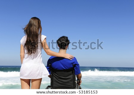 couple in love:  woman and husband in wheelchair on the beach - stock photo