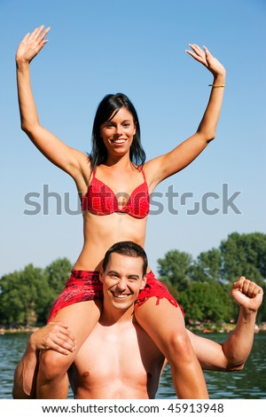 Couple in love - Woman in bikini sitting on her man's shoulders under blue sky - summer and fun - stock photo