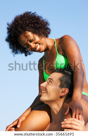 Couple in love - Woman of color in bikini sitting shoulders of her man under blue sky - summer and fun - stock photo