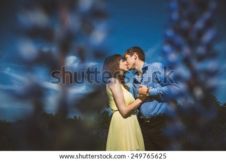 Couple in lupine flowers field embracing and smiling - stock photo
