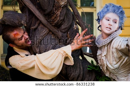 Couple in medieval costumes - male vampire reching hand to woman with blue wig