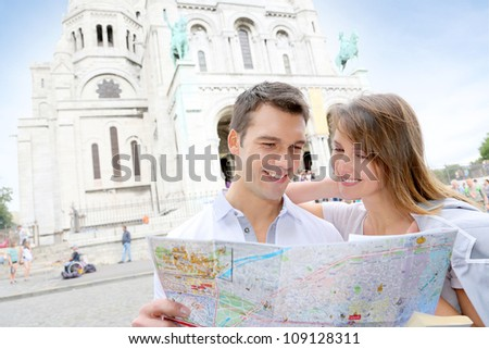 Couple in Montmartre reading tourist map - stock photo