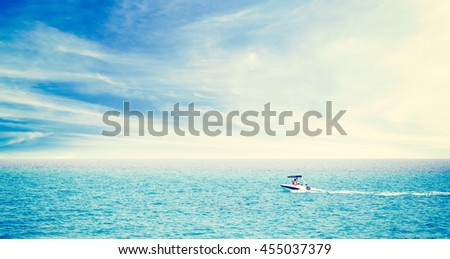 Couple in motorboat driving to horizon