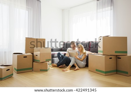 Couple in new apartment sitting on floor and using tablet - stock photo
