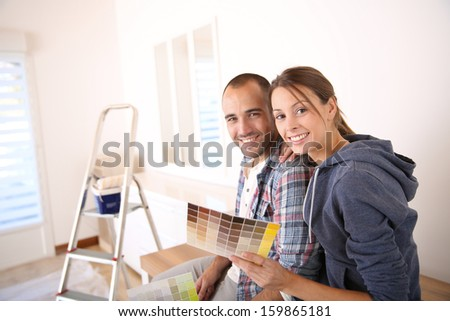 Couple in new house choosing color for walls - stock photo