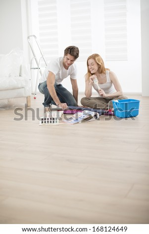 couple in new house choosing colors for walls - stock photo