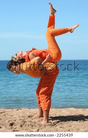 Couple in orange clothes having fun on the beach - stock photo