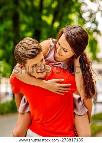 Couple  in orange t-shirt embracing at park. Summer outdoor. - stock photo