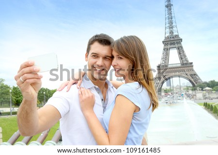 Couple in Paris taking pictures in front of Eiffel Tower - stock photo