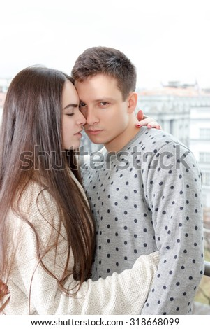Couple in passion hugging nose to nose on terrace , Youn woman and guy in love embracing each other touching noses outdoors - stock photo