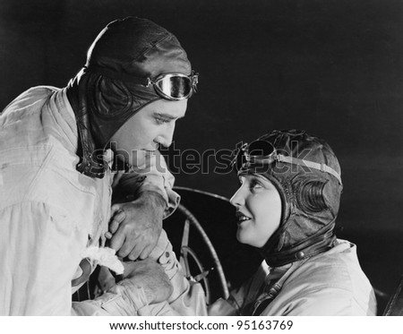 Couple in racing hats and goggles - stock photo