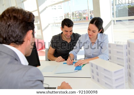 Couple in real-estate agency signing property loan contract - stock photo