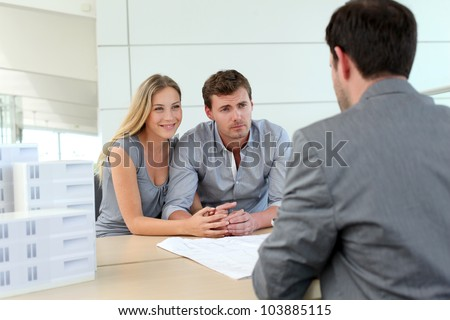 Couple in real-estate agency talking to construction planner - stock photo