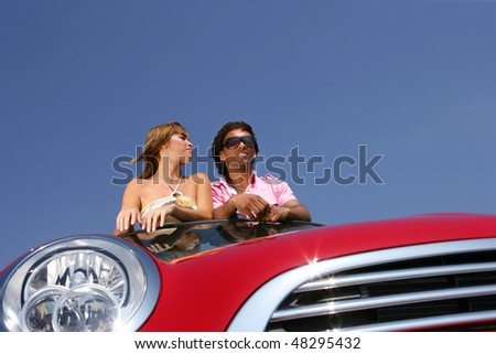Couple in red convertible car - stock photo