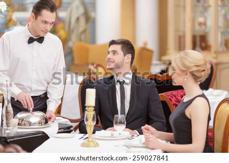 Couple in restaurant. Confident waiter serving the table with salad while beautiful couple looking at him and smiling while sitting in luxury restaurant with selective focus - stock photo