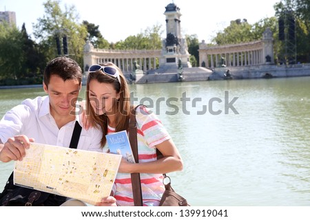 Couple in Retiro Park of Madrid looking at map - stock photo