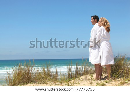 couple in robes on the beach - stock photo