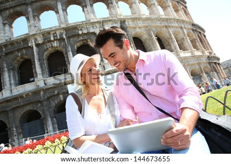 Couple in Rome using tablet to get tourist information - stock photo