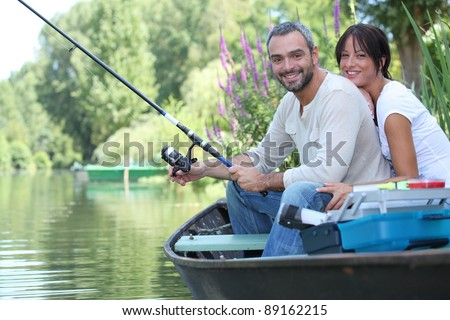 Couple in row boat fishing - stock photo