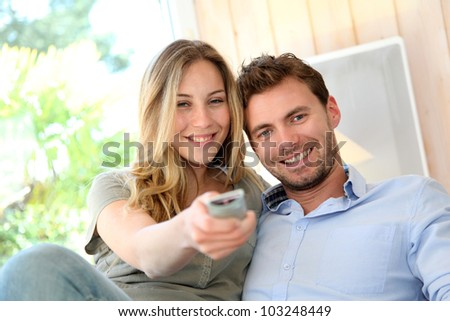 Couple in sofa watching tv - stock photo
