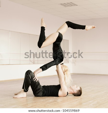 couple in sportswear in aerobics room performing tricks - stock photo