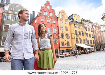 Couple in Stockholm, Sweden, Europe. Happy multiracial young couple walking outside on Stortorget big square in Gamla Stan, the old town of Stockholm. Scandinavian man, Asian woman. - stock photo