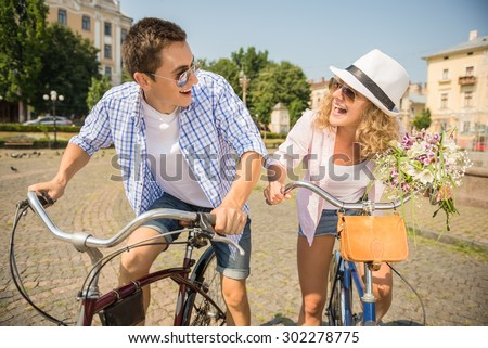 Couple in sunglasses riding on bicycles on the city street, looking to each other and having fun. - stock photo