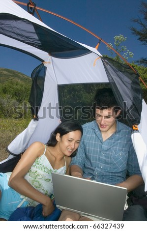 Couple in tent with laptop - stock photo