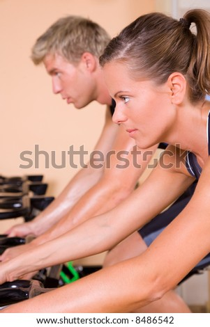 Couple in the gym cycling - stock photo