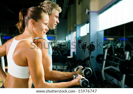 couple in the gym, rivaling each other, exercising with weights (focus on the face of the girl) - stock photo