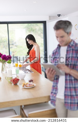 couple in the kitchen at the morning man using digital tablet at foreground - stock photo
