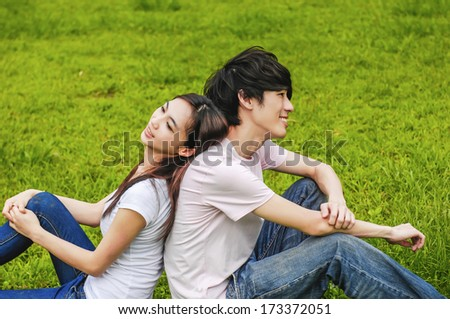 couple in the park sitting back to back - stock photo