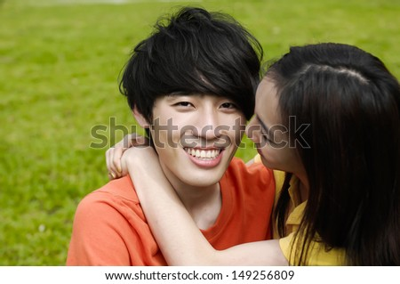 couple in the park sitting on the grass, have a good time together - stock photo