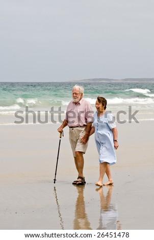 Couple in their eighties walking on beach - stock photo