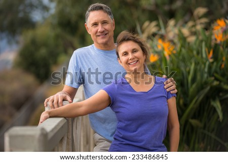 Couple in their fifties posing outside - stock photo