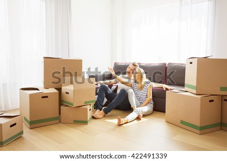 Couple in their new apartment sitting on floor - stock photo