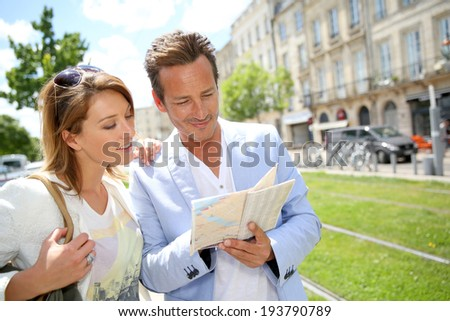 Couple in town looking at public transport map