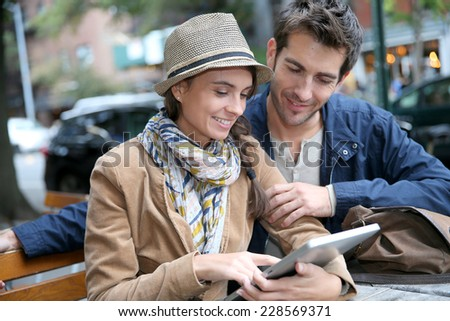 Couple in town sitting in coffee shop and using digital tablet - stock photo